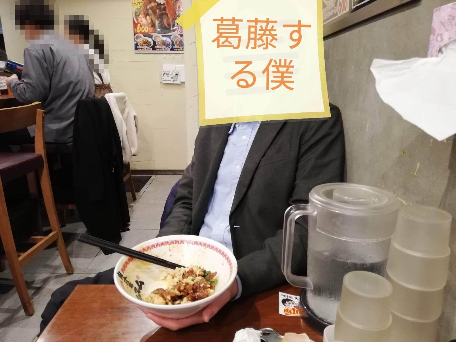 高田馬場『肉汁麺ススム』の肉汁丼の器を持つ男性の写真