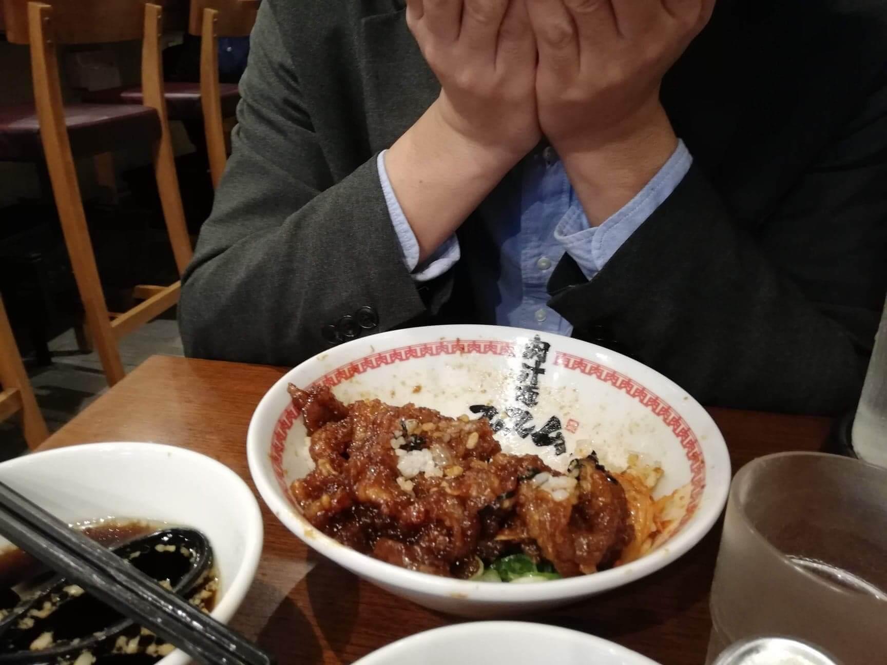 高田馬場『肉汁麺ススム』の肉汁丼の前で頭を抱える男性の写真