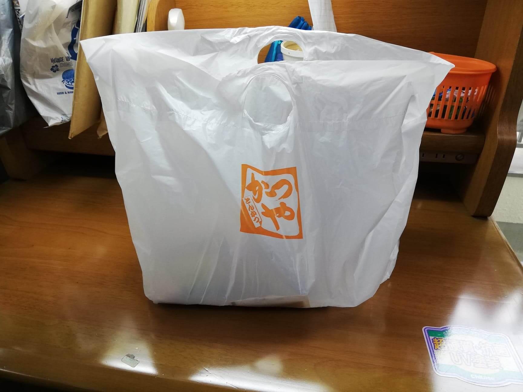 かつやの全力飯弁当『回鍋肉丼から揚げチキンカツ弁当』を机に置いている写真