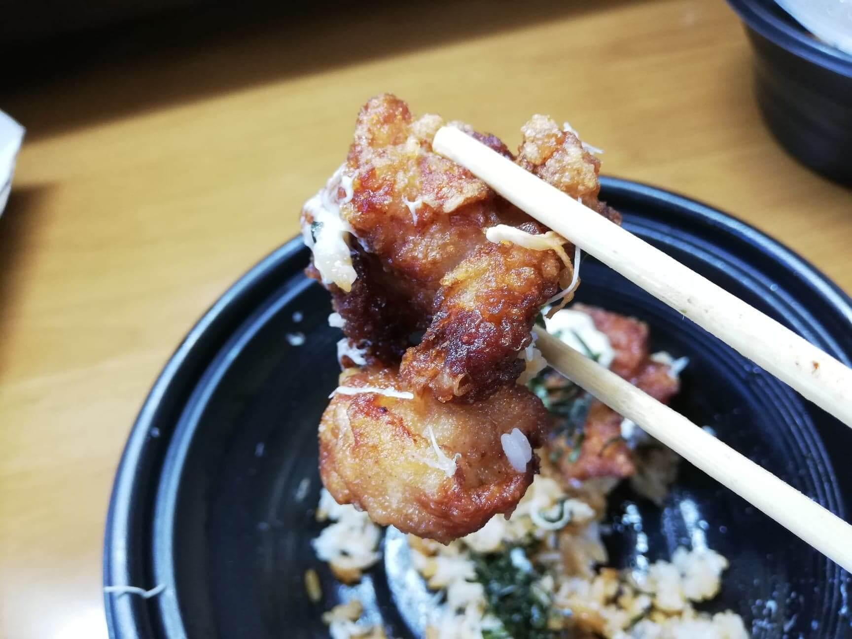 ガストのテイクアウトメニュー『ランチ唐揚げテリタル丼』の唐揚げを箸で持ち上げた写真