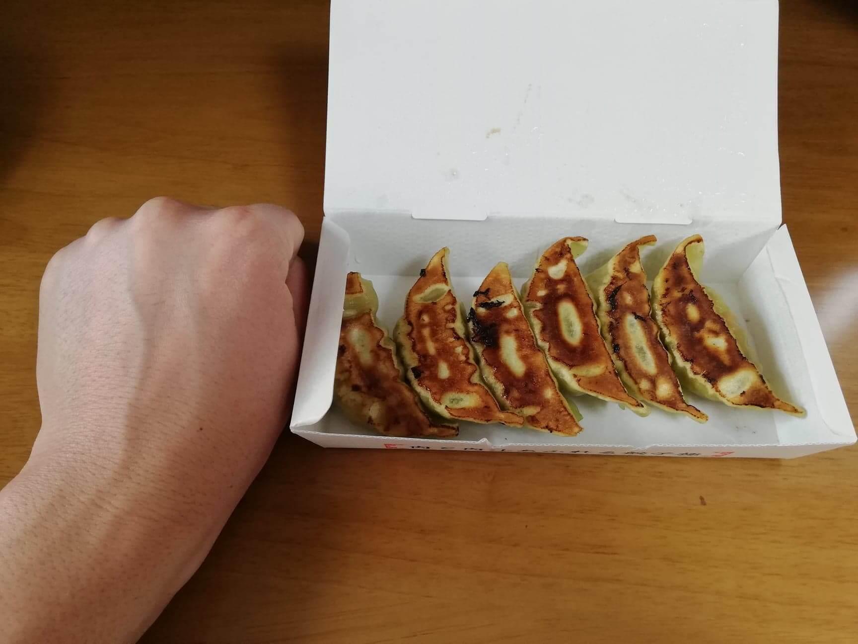 幸楽苑のテイクアウトメニュー『おみやげ焼きベジタブル餃子』と拳のサイズ比較写真