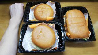 コメダ珈琲店の『カリーメンチカツバーガーとカリーコロッケバーガーとカツカリーパン』を拳とサイズ比較している写真
