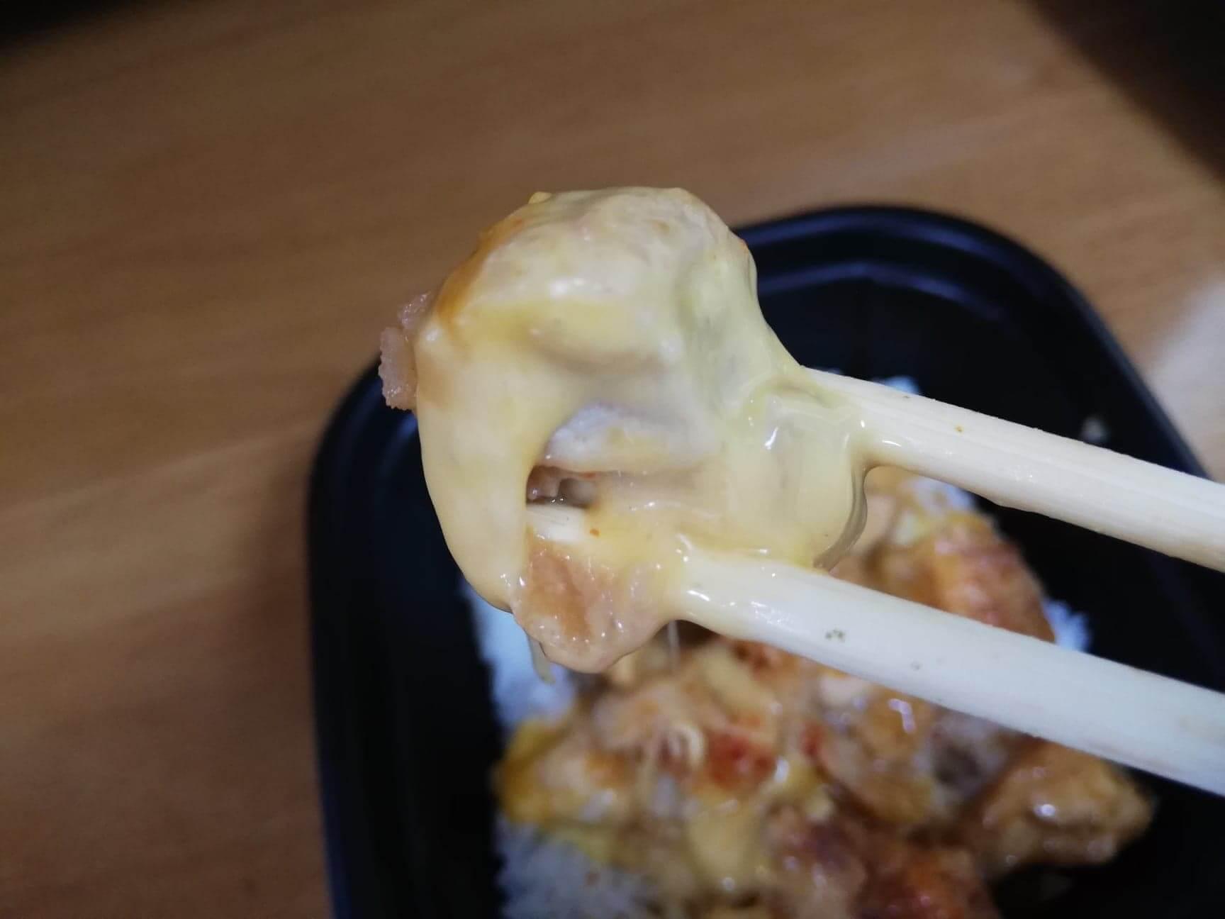 ファミマの『とろーりチーズの唐揚丼』の唐揚げを箸で持ち上げている写真
