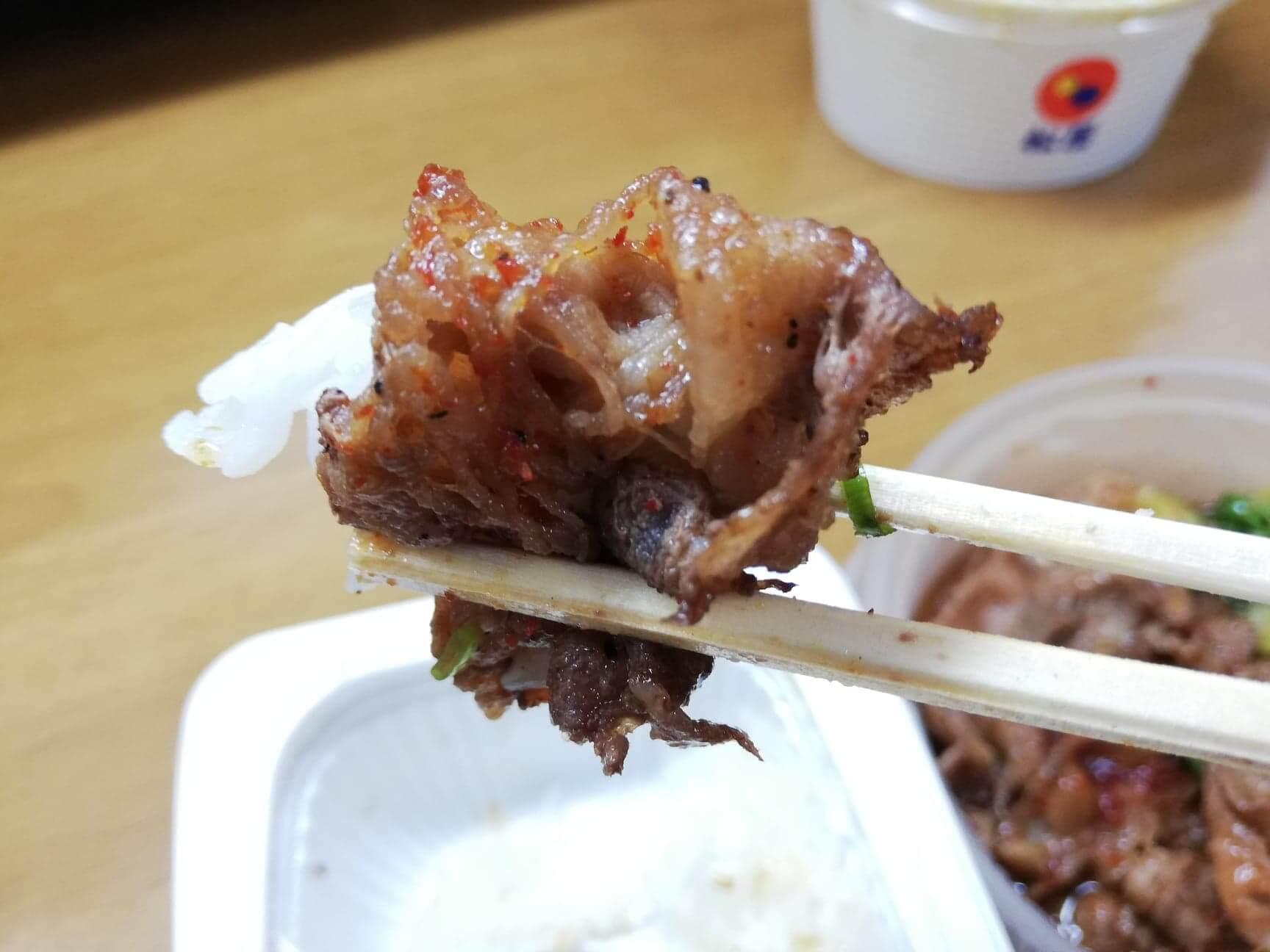 松屋のテイクアウト限定『おかずトリオ』のお肉たっぷり焼き牛めし皿のお肉を、箸で持ち上げている写真